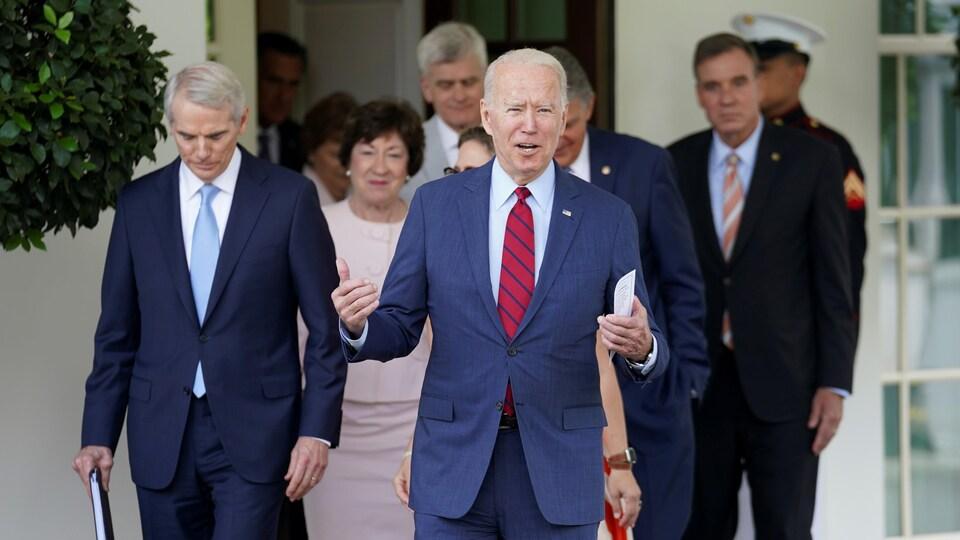 Un groupe d'hommes et de femmes à la sortie d'un bâtiment.