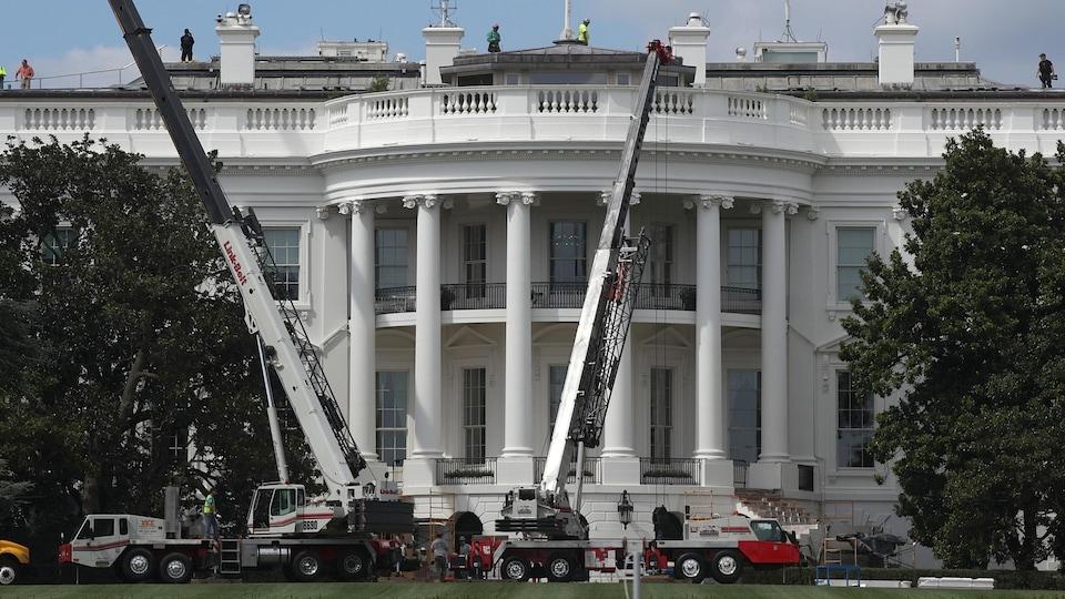 Grues et travailleurs de la construction au travail devant la façade de la Maison-Blanche.