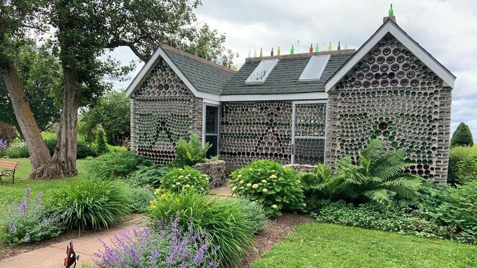 L'extérieur d'une maison faite en bouteilles de verre et le jardin autour.
