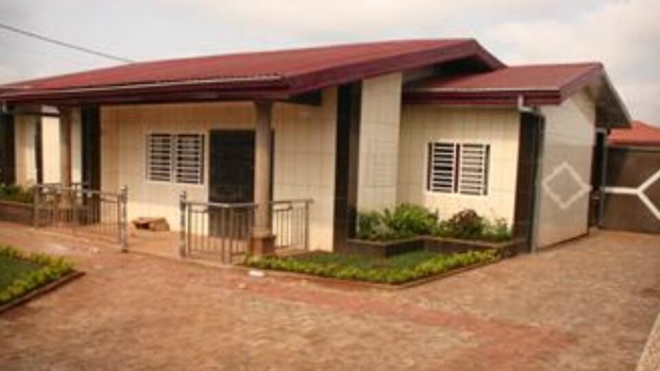 Photo d'une maison beige avec un toit et une entrée en pierres de couleur rouge.