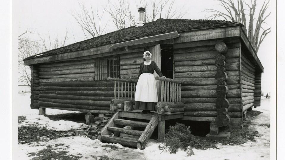 Une cabane en rondins munie d'un balcon sur lequel on voit une femme en costume d'époque.