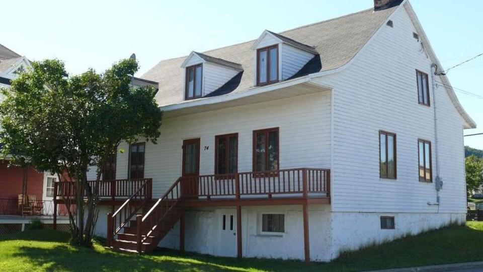 La maison est de style canadienne et possède trois étages : un sous-sol au niveau du sol, un rez-de-chaussée ainsi qu'un premier étage. Elle a un revêtement blanc et possède une galerie en bois faisant toute la longueur de la maison.