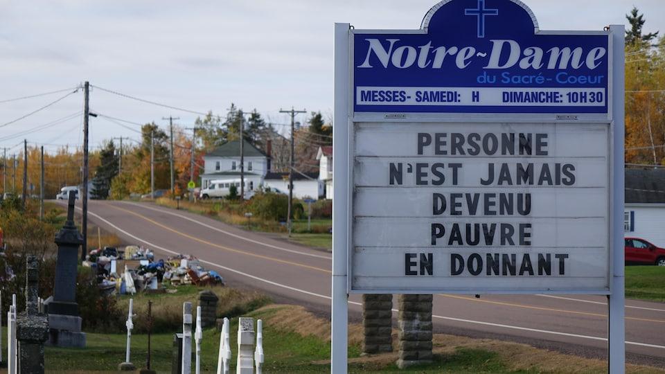 Une affiche de l'église où on peut lire «Personne n'est jamais devenu pauvre en donnant» et où on voit la vente de garage au loin.