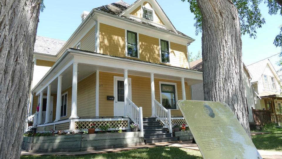 Une grande maison de couleur jaune clair, un jour d'été ensoleillé.