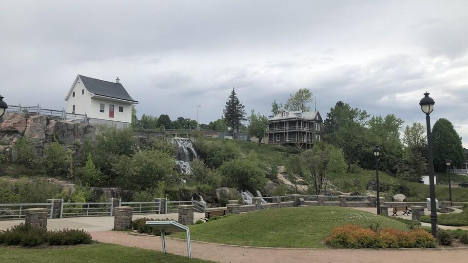 Deux maisons ancestrales se trouvent près d'une petite chute.