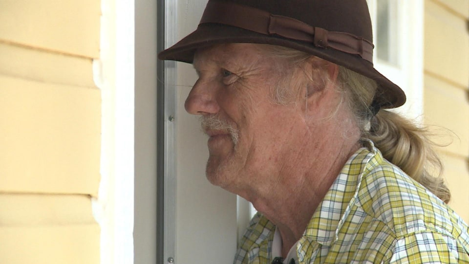 L'homme est photographié près de la maison et porte un chapeau en feutre.