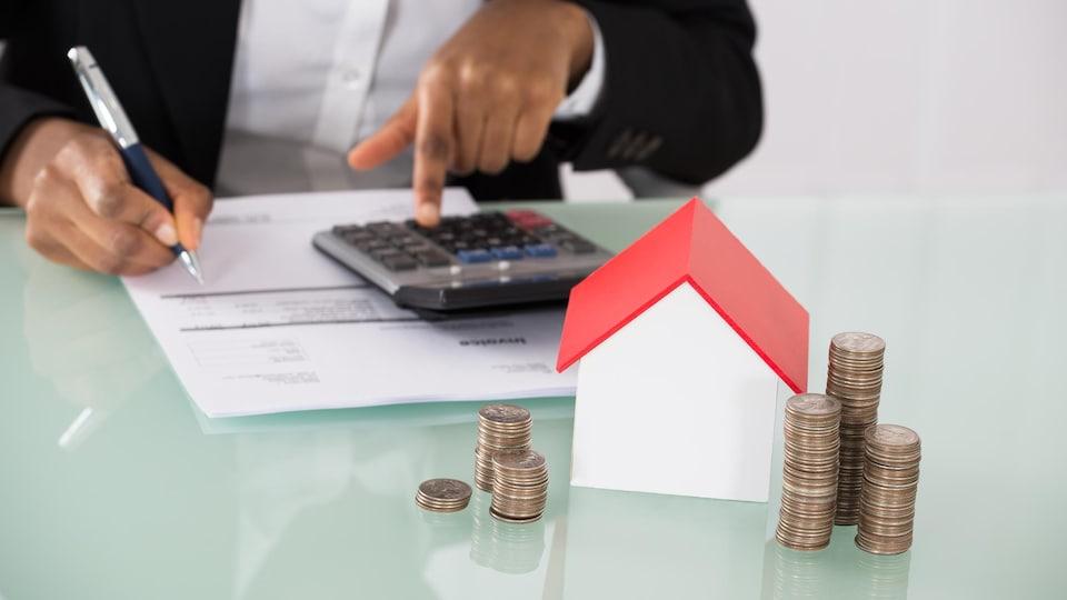 Un homme effectue des calculs et devant lui se tient une petite maison avec des pièces de monnaie.