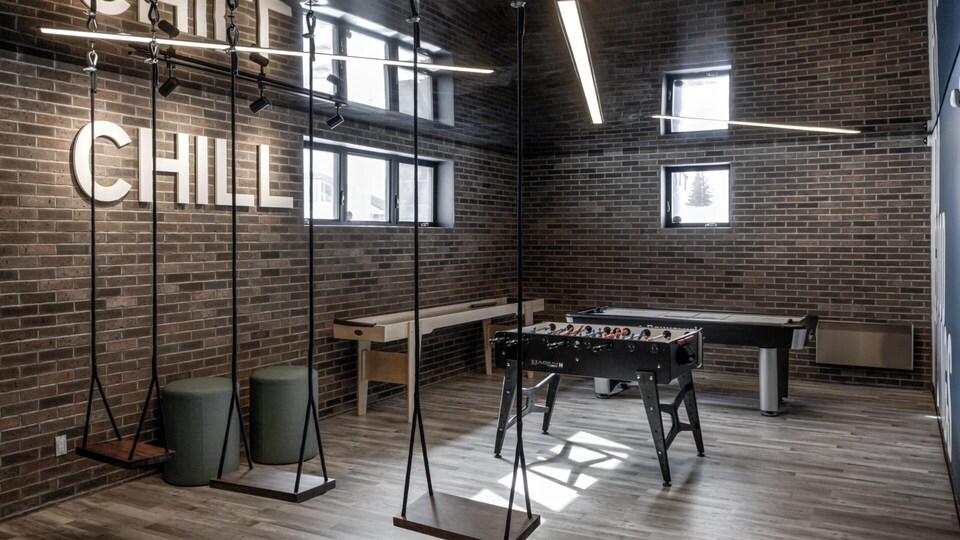 Une salle avec trois balançoires et une table de baby foot.