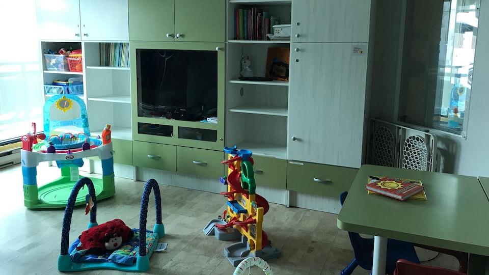Des jouets pour enfants jonchent le sol de la salle de jeux, munie de grandes armoires et d'une télévision.