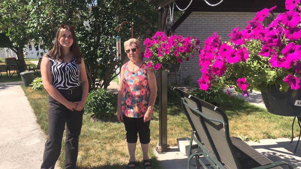 Frédérique Turcotte et Madeleine Ouellet sont devant des jardinières de fleurs.