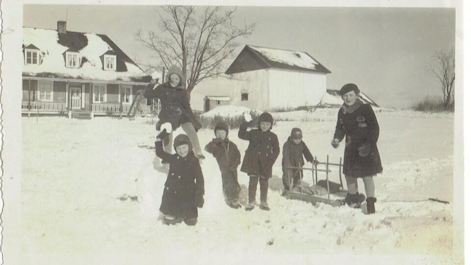 Des enfants qui s'amusent devant la maison durant l'hiver.