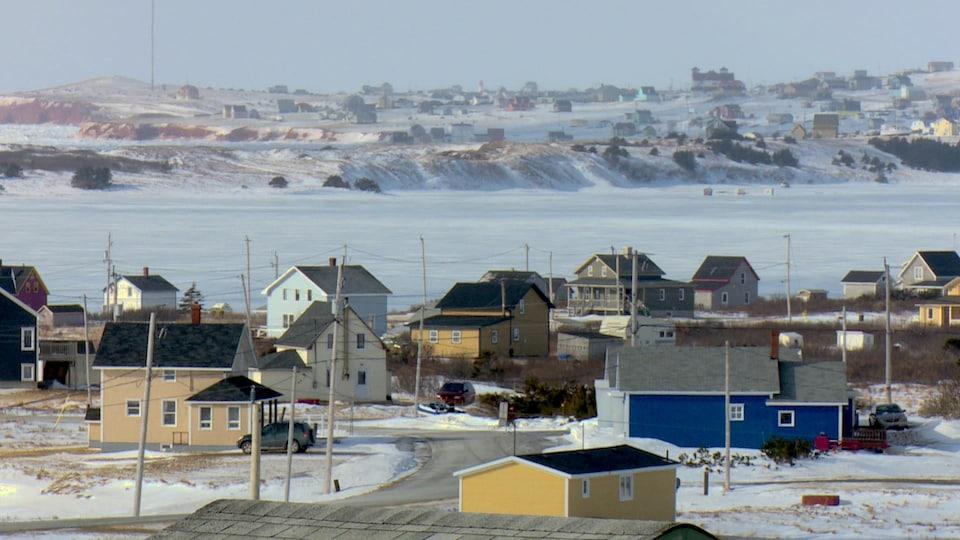 Quelques maisons colorées dans le décor enneigé des Îles-de-la-Madeleine.