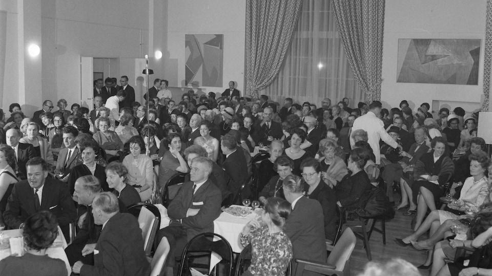 Public de l'émission Chez Miville, tenue soignée, dans la grande salle de la Maison du Québec à Paris.