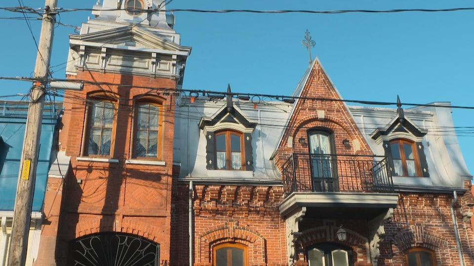 La façade d'une maison avec de petits galeries au 2e étage et des lucarnes.