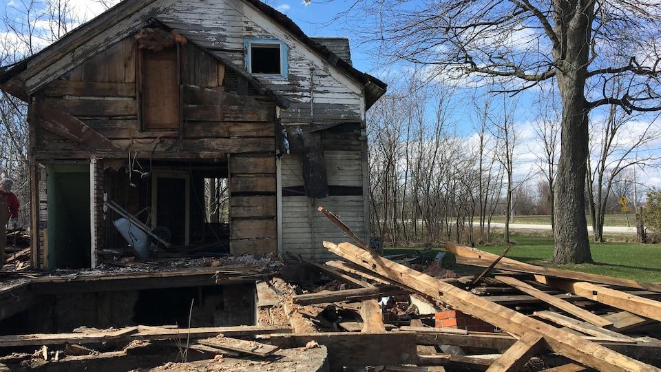 Maison dont certains murs sont ouverts. Beaucoup de morceaux de bois sont en avant.