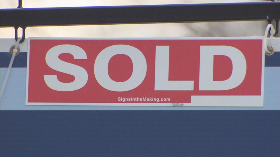 Photo d'une affiche avec la mention « vendue » devant une maison