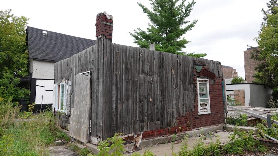 Une maison en brique dont le toit a été arraché et dont la quasi-totalité de la brique a été arrachée.