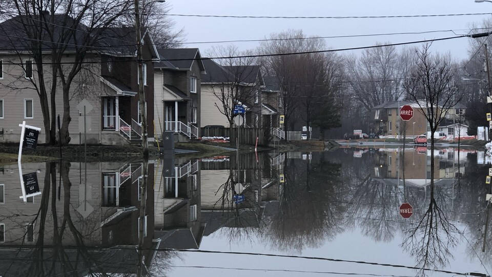 Des maisons dans une rue submergée par les eaux.