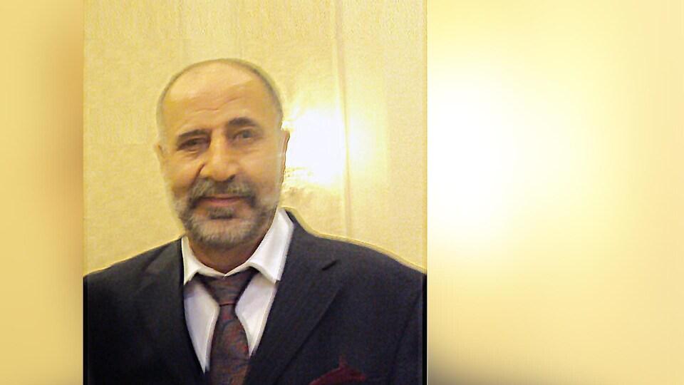 Portrait de Majeed Kayhan habillé en costume et cravate.
