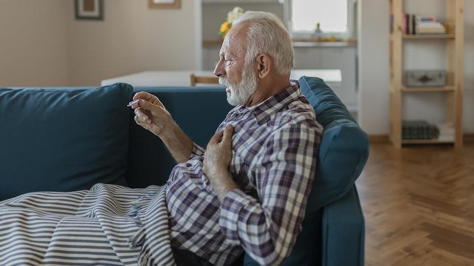 Un vieil homme étendu sur son divan prend sa température.