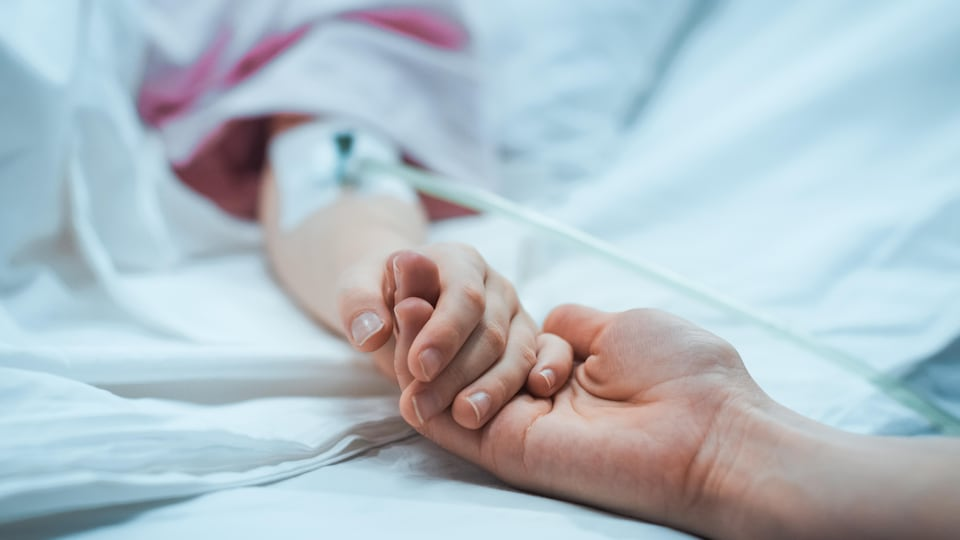 Une personne tient la main d'un malade dans un lit d'hôpital.