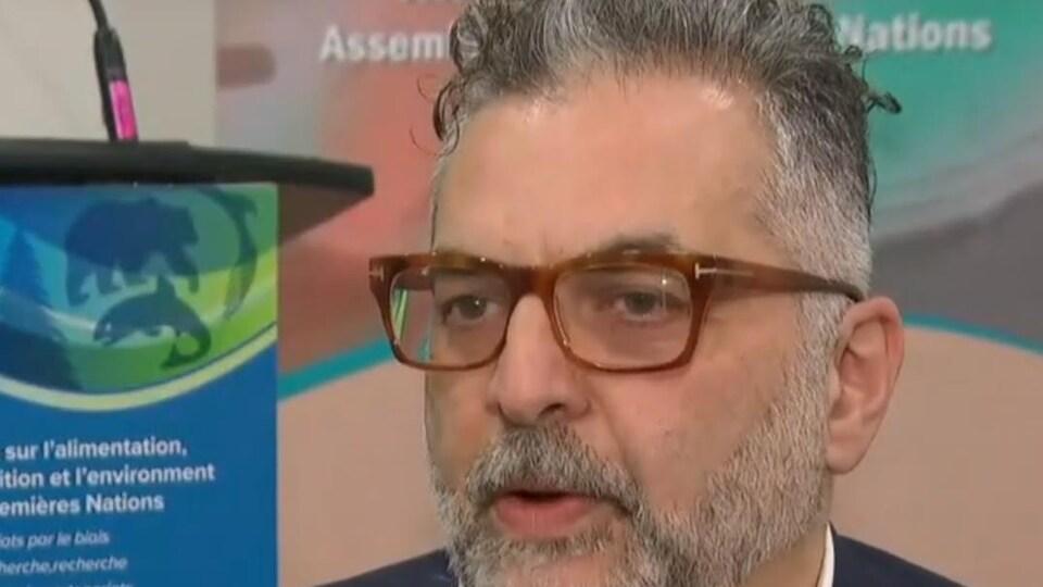 Un homme aux cheveux gris qui porte des lunettes