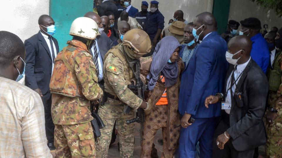 Des militaires escortent un homme portant un foulard sur la tête.