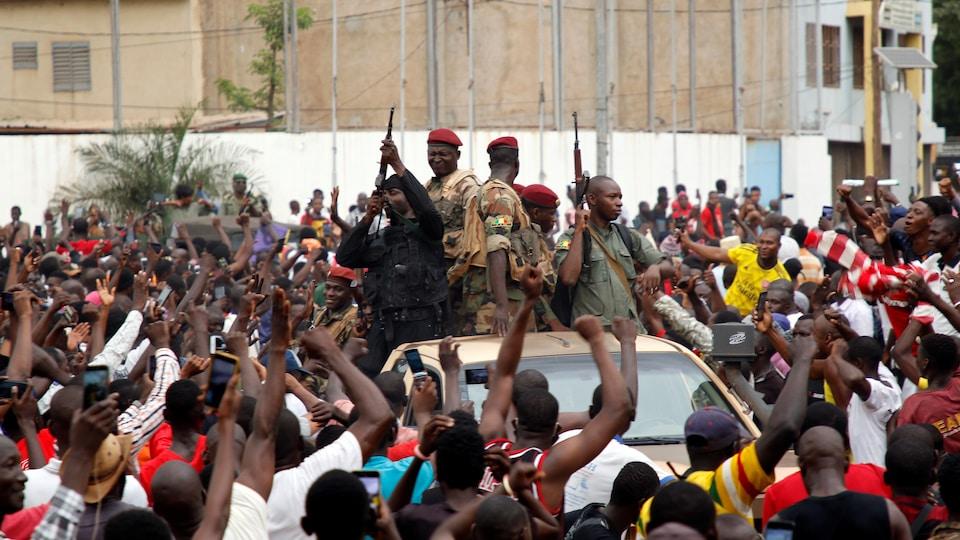 Des soldats debout sur un véhicule au milieu de centaines de personnes.