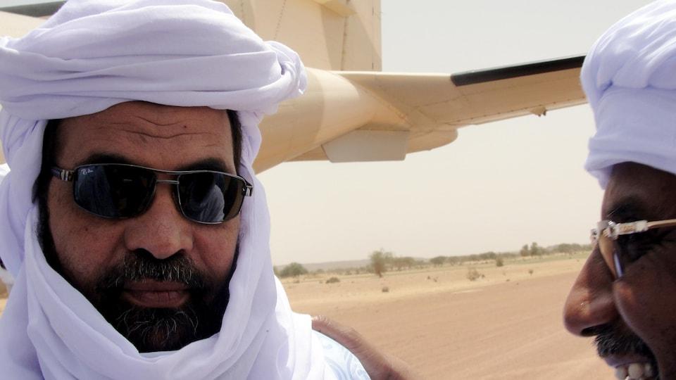 Un homme portant des lunettes de soleil, la barbe et un chèche blanc discute avec un autre homme vêtu de la même façon près d'un avion, au Mali.