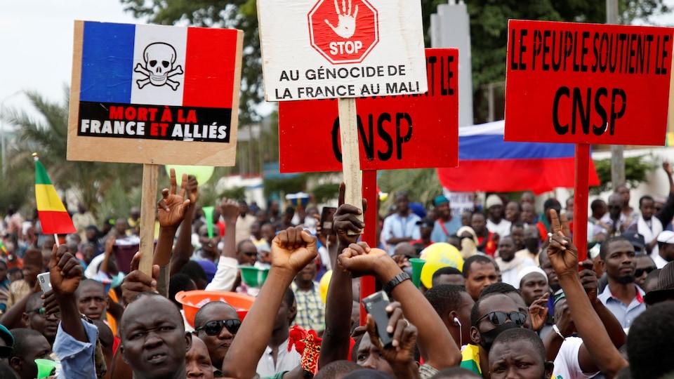 Des manifestants maliens brandissent des pancartes sur lesquelles sont écrits des slogans favorables aux militaires putschistes et hostiles à la France.