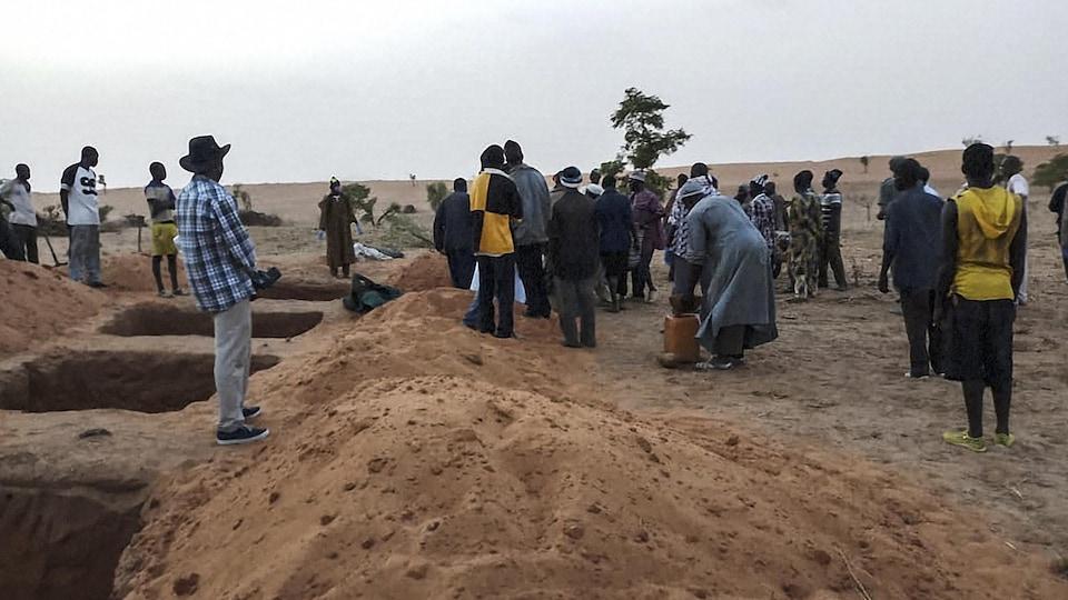 Plusieurs Maliens sont debout près de fosses creusées dans le sable.