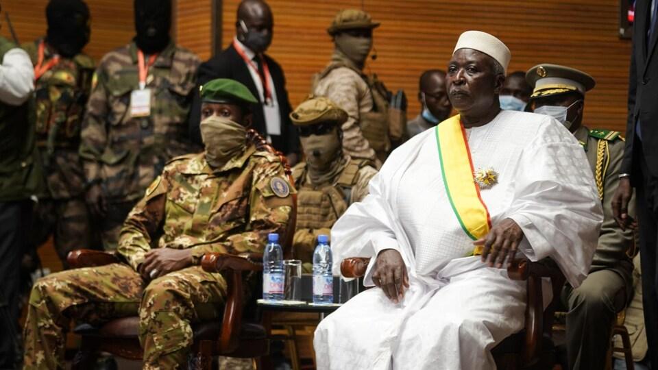 Le président, vêtu en blanc, est assis à côté du vice-président, en treillis militaire. Plusieurs militaires en uniforme sont derrière eux.