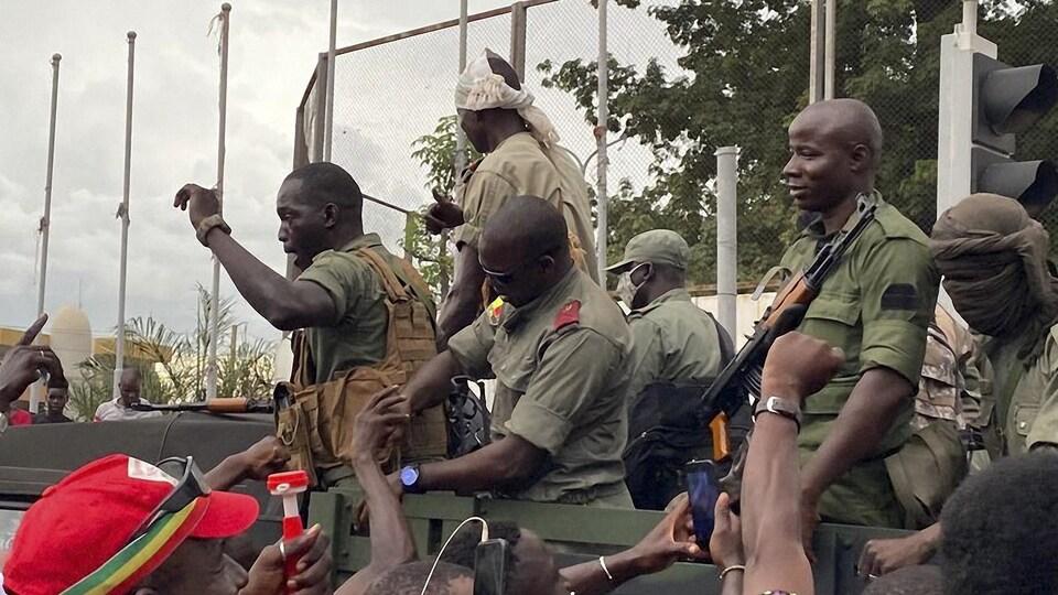 Des soldats à bord d'un camion au milieu d'une foule de manifestants