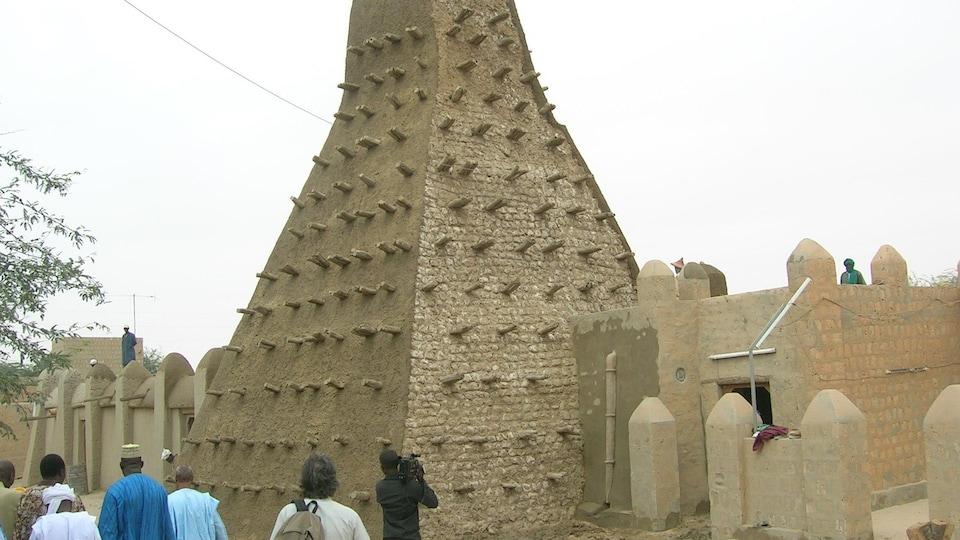 Un groupe des personnes contemplent un bâtiment en brique avec un minaret assortit des morceaux des bois.