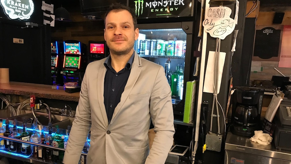 Mathieu Malouin, portant une chemise et un veston, derrière le bar de son établissement rue Sainte-Catherine et souriant devant la caméra.