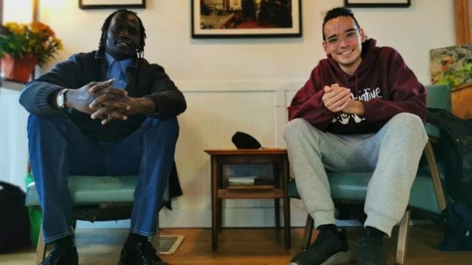 Deux hommes assis, qui sourient à la caméra.