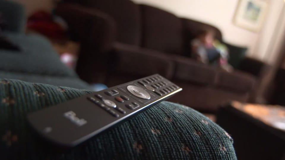 Une manette de télévision de Bell repose sur le bras d'un fauteuil.