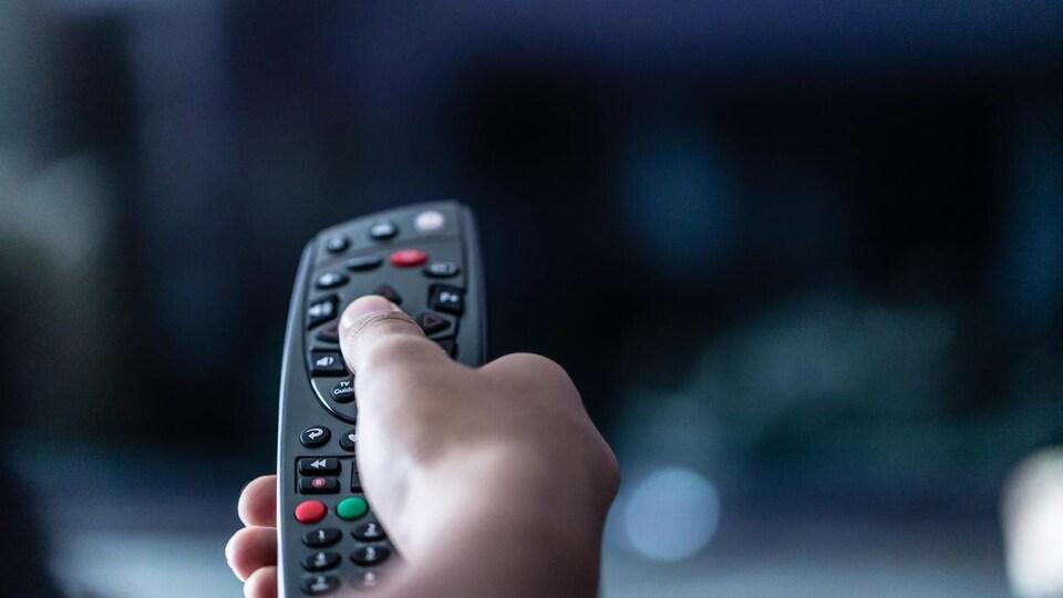 Une main tient une télécommande.