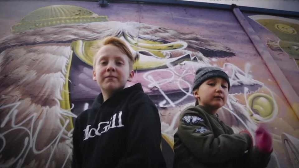 Un jeune garçon portant en coton ouaté avec l'inscription « McGill », logo de l'université, et une jeune fille, à sa droite, sont devant un mur où l'on a peint des graffitis sur une murale.