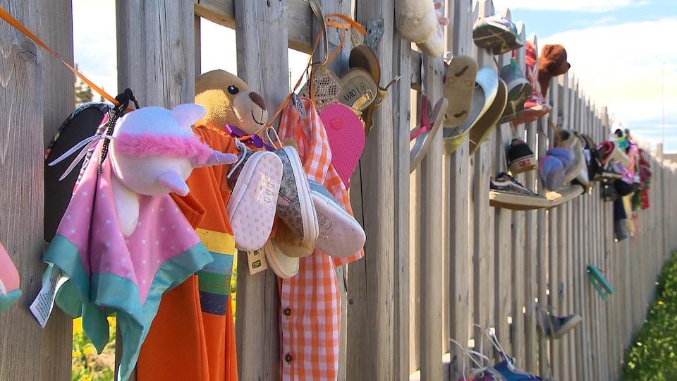 Peluches et souliers accrochés à une clôture par une journée ensoleillée.