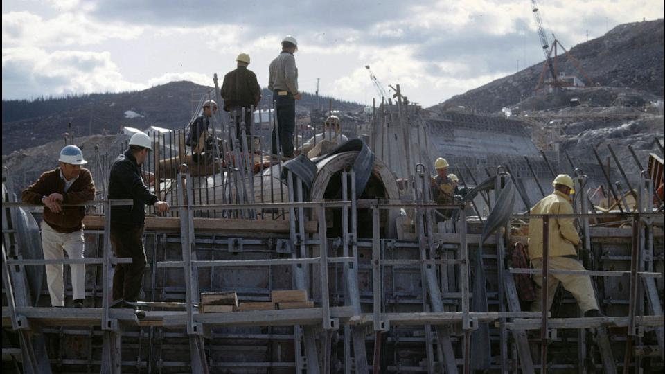 Des travailleurs sur des échafauds pendant la construction du barrage.
