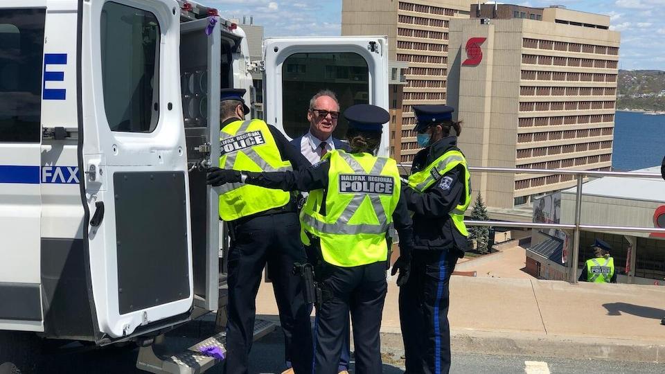 Trois policiers et un homme en veston et cravate autour d'un fourgon de la police.