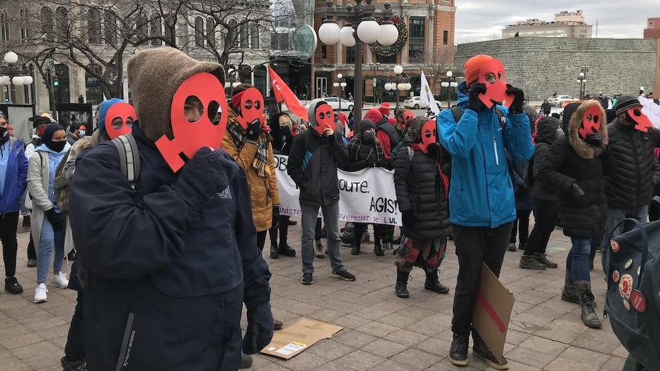 Des personnes portent un masque rouge en carton pour dénoncer le plan vert.