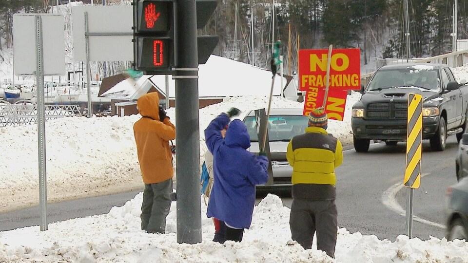 Des gens avec des pancartes dans la neige