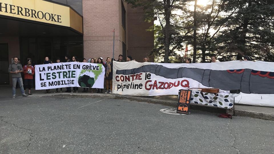 Des manifestants avec des banderoles sur lesquelles est inscrit : La planète en grève, l'Estrie se mobilise et Contre le pipeline Gazoduq.