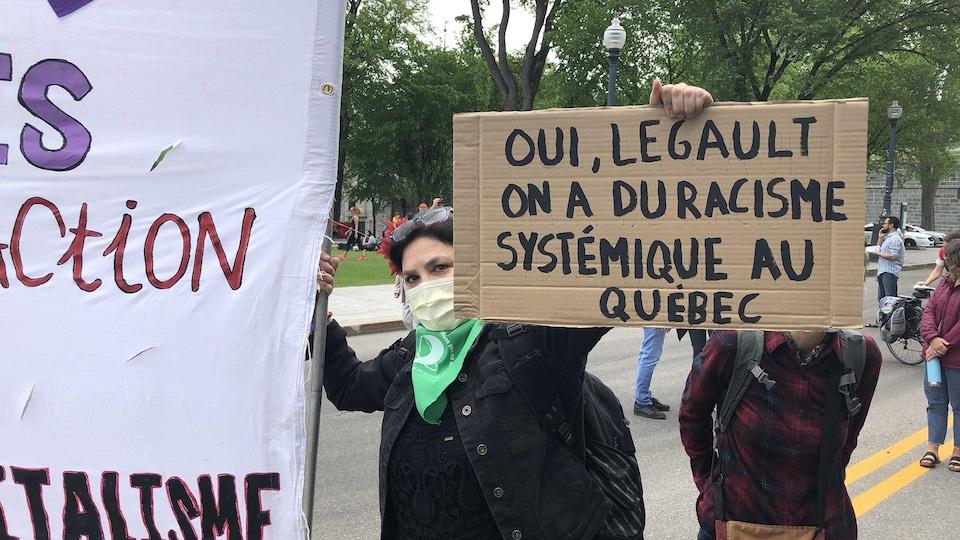 Une femme tient une pancarte où on peut lire « Oui, Legault, on a du racisme systémique au Québec » lors d'une manifestation devant l'Assemblée nationale.