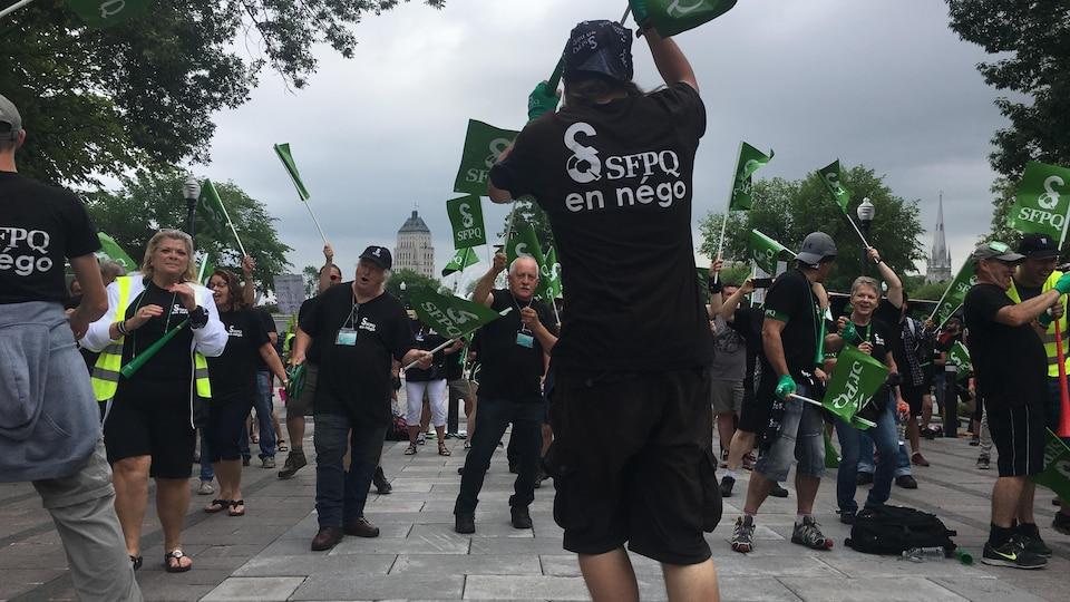 Des manifestants qui brandissent des drapeaux dans les airs.