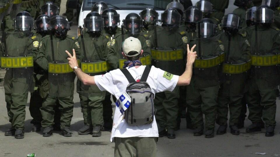 Un jeune homme fait le signe de la paix en levant les deux bras devant un cordon de policiers.