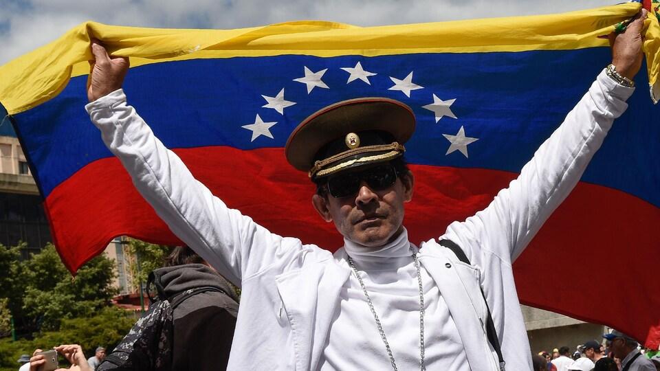 Un manifestant coiffé d'une casquette militaire brandit un drapeau dans les rues de Caracas pour protester contre le gouvernement Maduro.