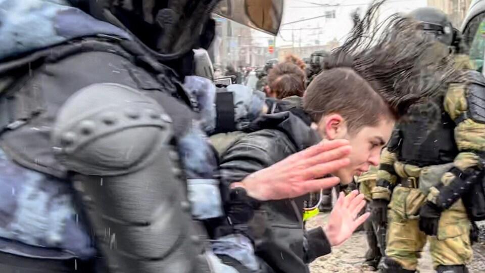On voit un policier qui escorte un manifestant en le prenant par les bras, dans une rue enneigée.